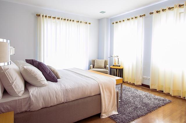 postel s polštáři v pokoji se závěsy a chlupatým kobercem